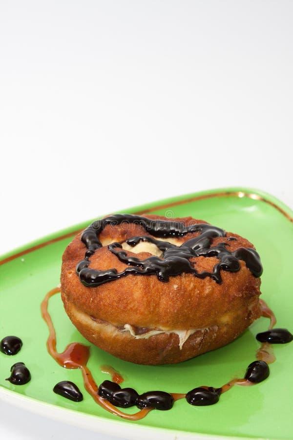 Donut mit Schokoladencreme und Erdbeercreme auf einer Platte lizenzfreies stockbild
