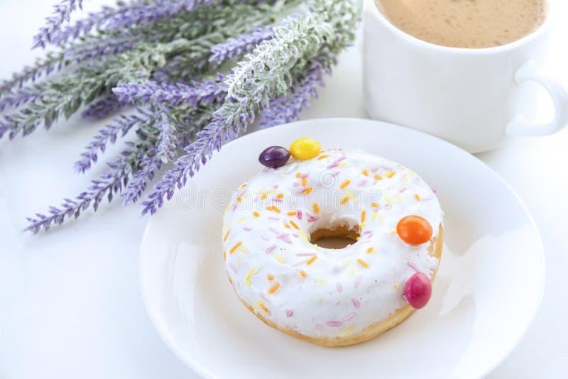 Donut mit weißer Zuckerglasur auf der Platte von mehrfarbigen Geleebonbons, das Farbpurpur, Lavendel, weiße Kaffeetasse stockbild