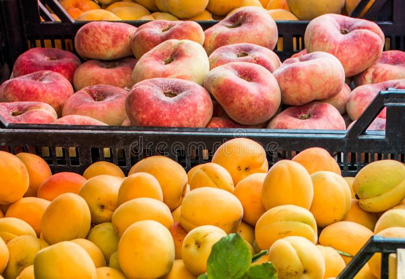 Donut peaches and big apricots in plastic boxes at street fruit market royalty free stock photography