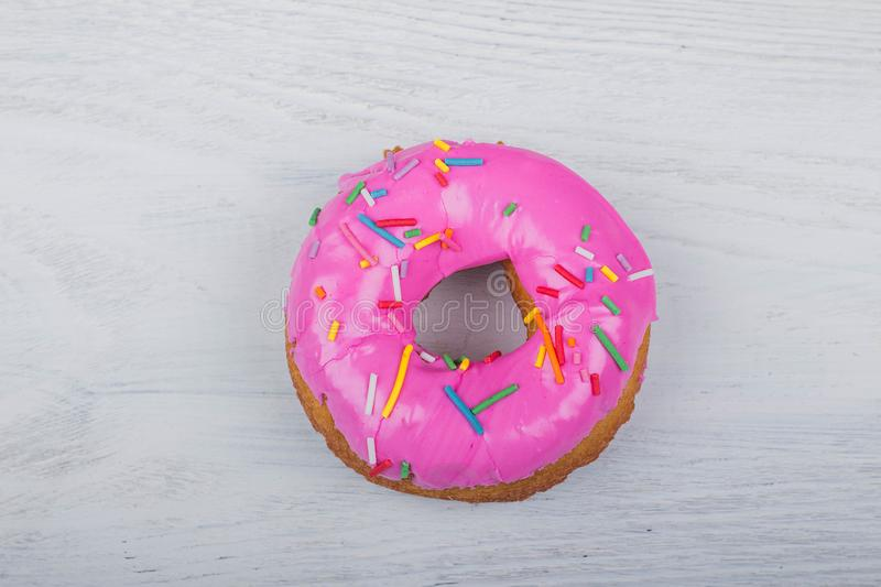 Donut with pink glaze on white wooden background royalty free stock image