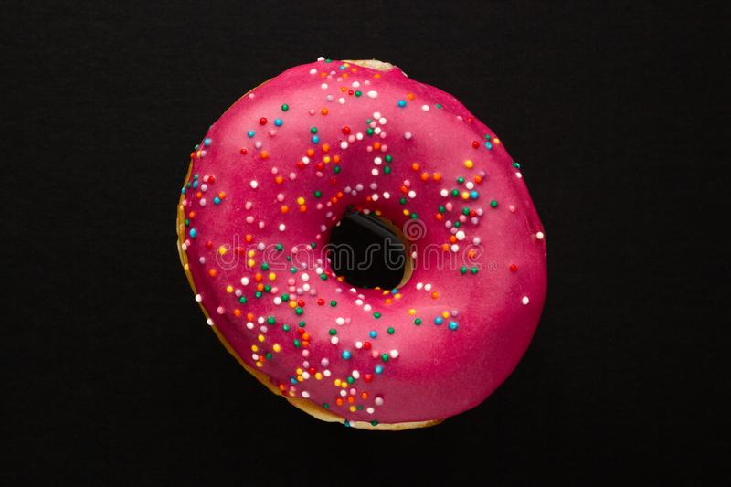 Donut pink with sprinkles isolated on black background, close-up royalty free stock photos