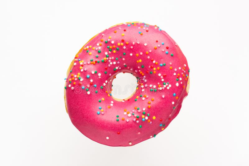 Donut pink with sprinkles isolated on white background, close-up royalty free stock photography