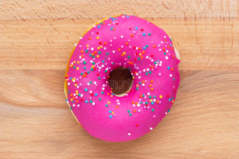 Donut pink with sprinkles isolated on wooden background royalty free stock photos