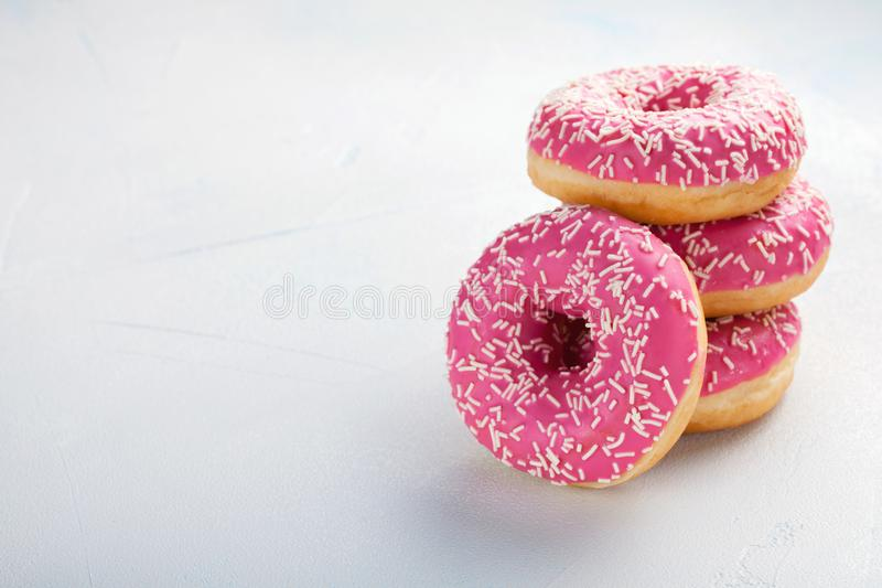 Donut. Sweet icing sugar food. Dessert colorful snack. Treat from delicious pastry breakfast. Bakery cake. Doughnut with frosting. Baked unhealthy round on a stock photos