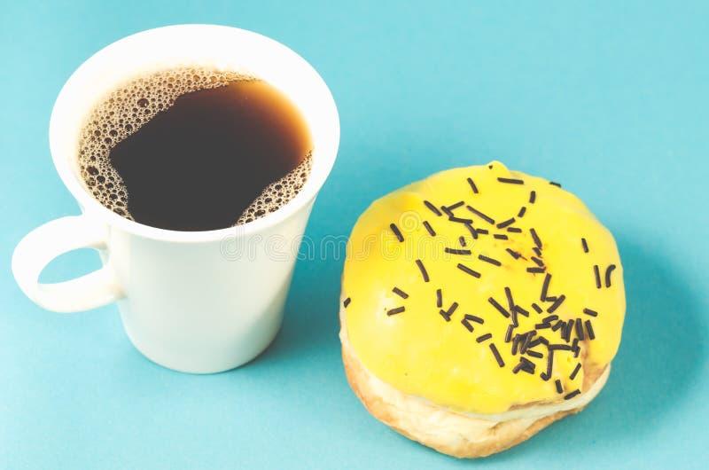 Donut und coffe Schale lokalisiert auf blauem Hintergrund/Donut im Gelb lizenzfreie stockfotos