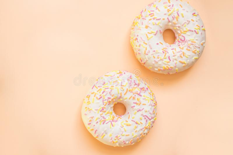 Donut with white icing colored topping, isolated on yellow background.Tasty classic two glazed donuts isolated.Delicious stock photography