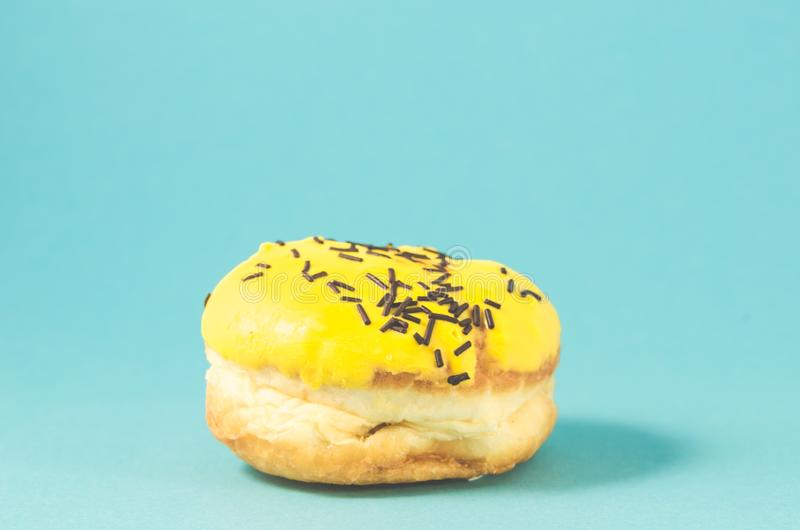 Donut in yellow glaze on blue background/Donut in yellow glaze decorated with dark chocolate sticks on blue background, selective. Focus, pink, berliner, icing stock photography