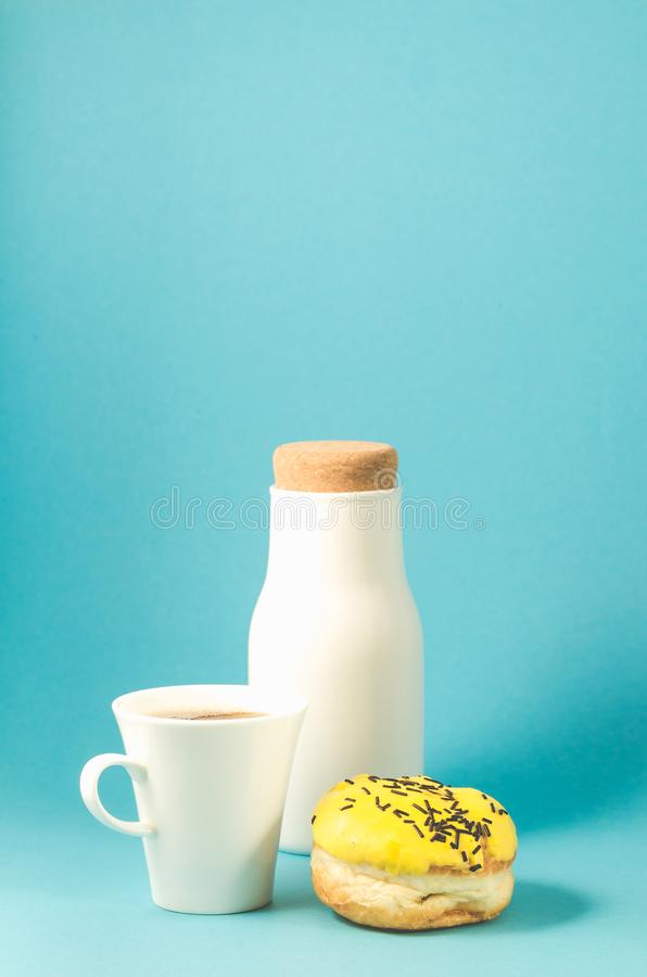 Donut in yellow glaze, coffe cup and bottle on blue background/Donut in yellow glaze decorated with dark chocolate sticks, coffe. Cup and bottle on blue stock photography
