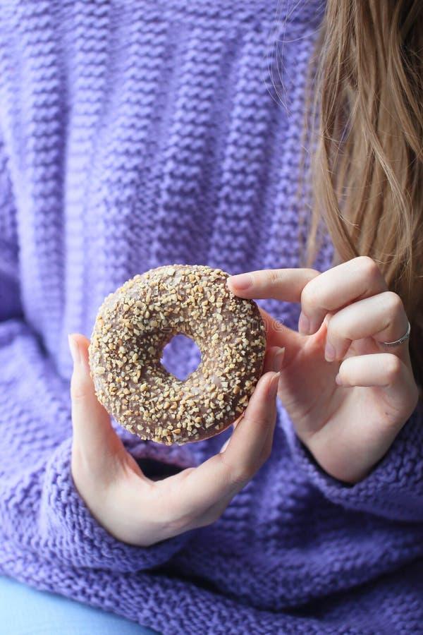 Donuts με τα καρύδια στα χέρια των γυναικών στοκ φωτογραφία με δικαίωμα ελεύθερης χρήσης