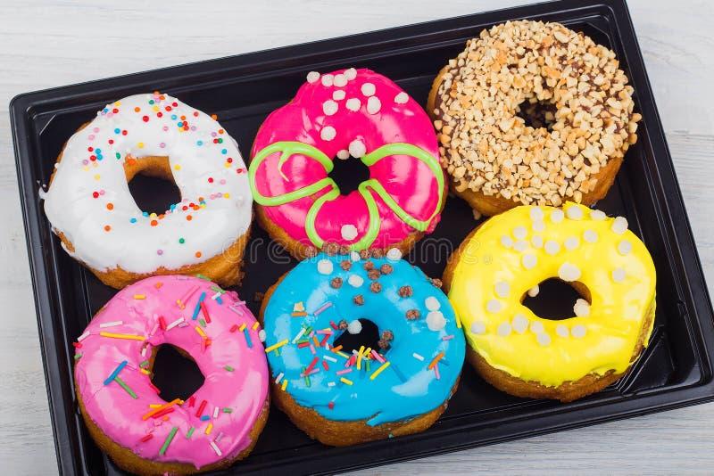 donuts με το λούστρο σε ένα κιβώτιο σε ένα άσπρο ξύλινο υπόβαθρο στοκ εικόνες