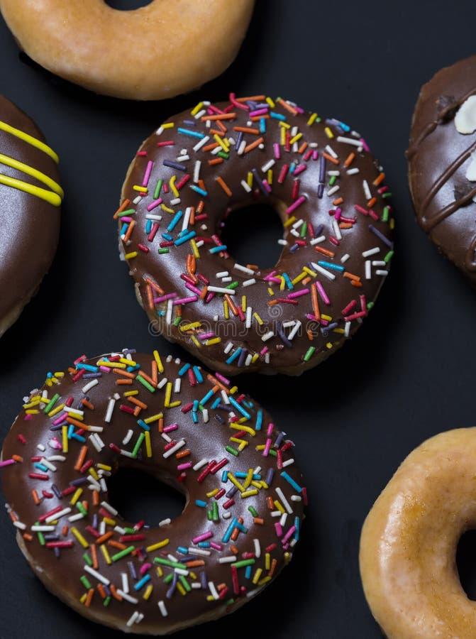Donuts που προετοιμάζεται με το αλεύρι, το λούστρο, τη σοκολάτα και τους ζωηρόχρωμους σπινθήρες στοκ εικόνες με δικαίωμα ελεύθερης χρήσης