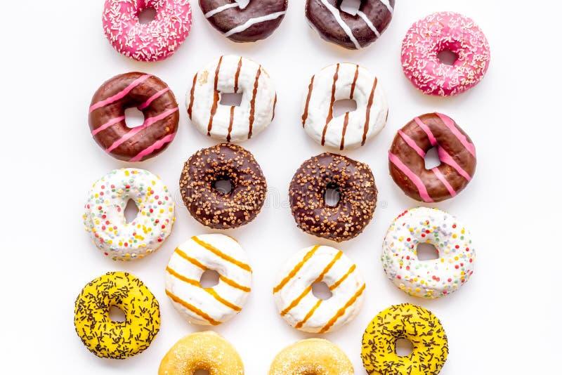 Donuts των διαφορετικών γεύσεων για το πρόγευμα στην άσπρη τοπ άποψη υποβάθρου στοκ φωτογραφίες