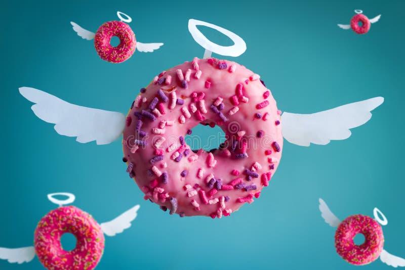 donuts ангела с крыльями белой бумаги и nimbus на голубой предпосылке, милой праздничной картой стоковая фотография rf