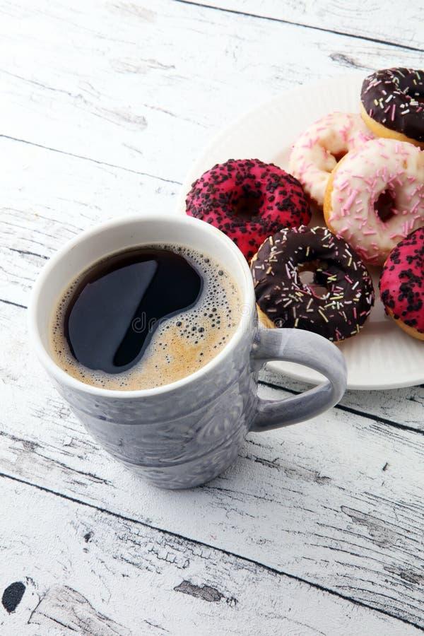Donuts и кофе для сладостного завтрака на деревянной предпосылке стоковые изображения