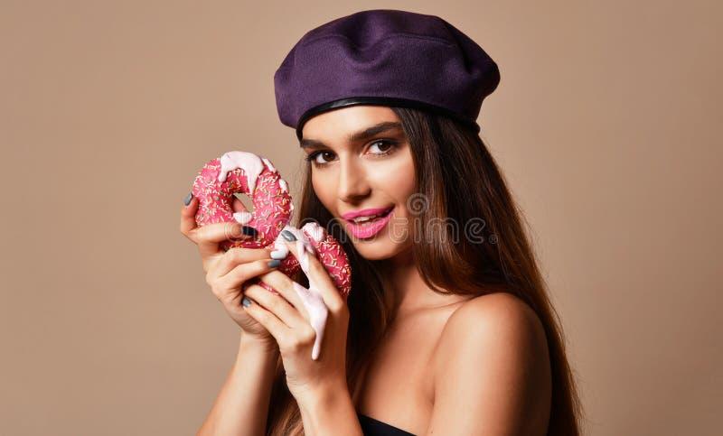 Donuts сахара владением женщины рот сладких розовых голодный на русой предпосылке стоковая фотография rf