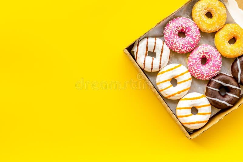 Donuts с различными вкусами в коробке на желтом модель-макете взгляда сверху предпосылки стоковая фотография