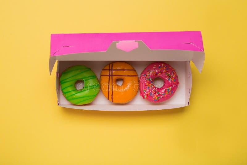 Donuts цвета в коробке на желтой предпосылке открытый космос стоковые изображения