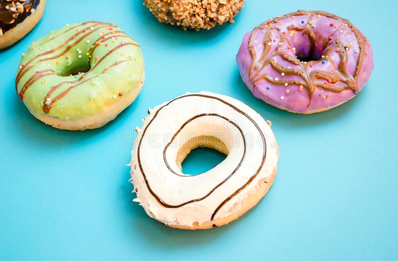 Donuts assorted with glazed on blue and pink. Background stock photo