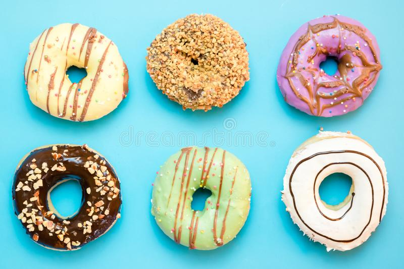 Donuts assorted with glazed on blue and pink. Background stock photos