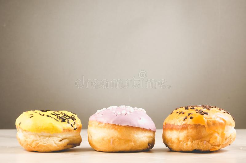 Donuts. Assorted donuts lying on a white table on background with copy space. Ð¡oncept sweet food stock images