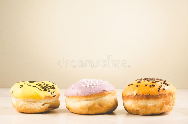 Donuts. Assorted donuts lying on a white table on background with copy space. Ð¡oncept sweet food stock image