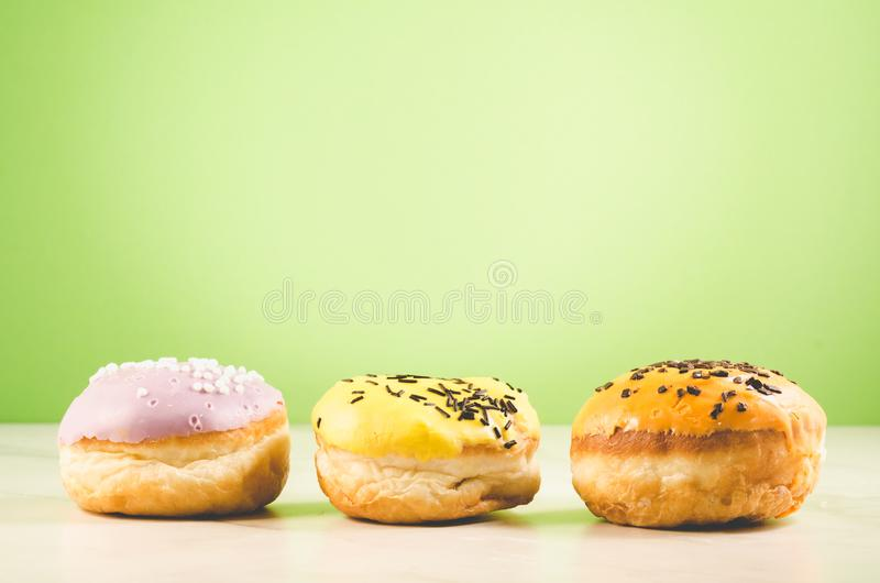 Donuts. Assorted donuts lying on a white table on green background. Ð¡oncept sweet food royalty free stock photo