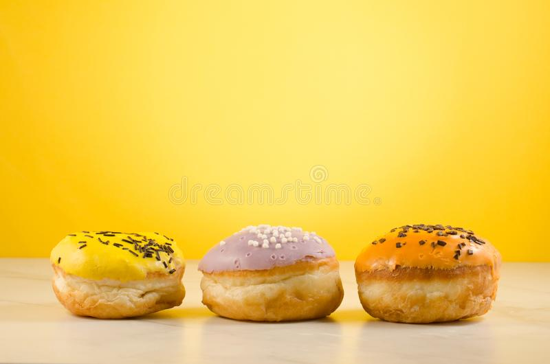 Donuts. Assorted donuts lying on a white table on yellow background. Ð¡oncept sweet food stock images