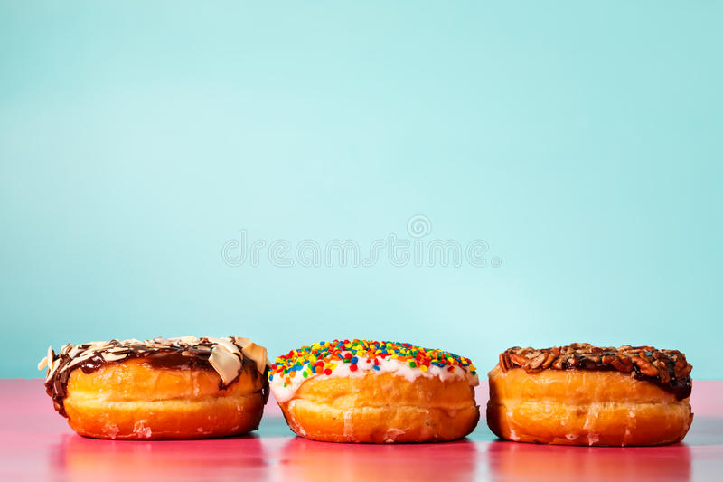 Donuts. Assorted donuts on pastel blue and pink background stock photos