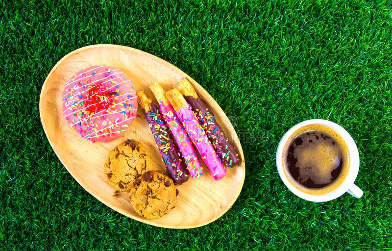 Donuts and black coffee on grass stock image