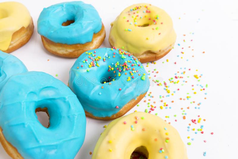 Donuts with blue and yellow glaze on a white background stock photo
