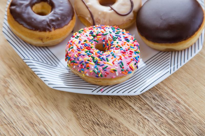 Donuts in box. Delicious colorful donuts on dish on wooden background stock images