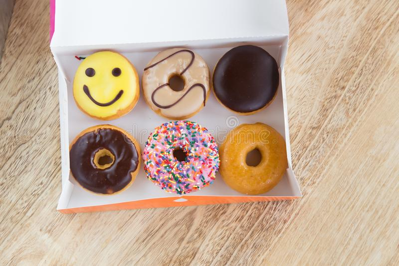 Donuts in box. Delicious colorful donuts in box on wooden background royalty free stock image