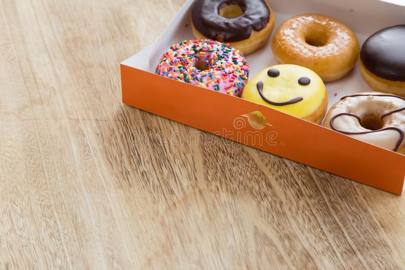 Donuts in box. Delicious colorful donuts in box on wooden background royalty free stock photo