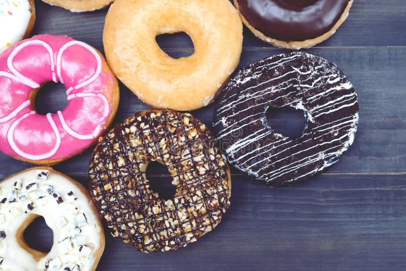 Donuts and chocolates have good taste on wooden floors. Assorted donuts with chocolate frosting, sprinkles donuts Colorful variety and Variety of flavors on a stock images