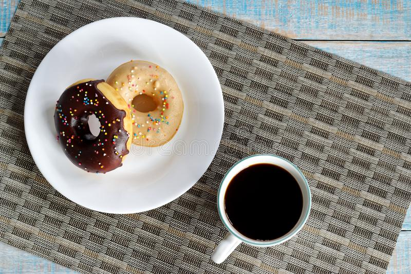 Donuts and coffee on wooden table. Top view with copy space royalty free stock images