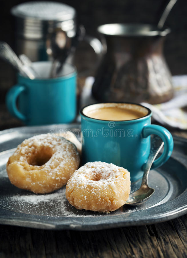 Donuts and cup of coffeee. Donuts and cup of coffee on dark wooden table royalty free stock photo
