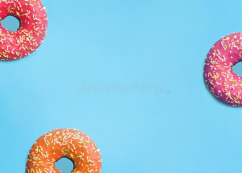 Donuts of different colors on a blue background. Sweet donuts - Flat position, top view, copy space-image royalty free stock photos