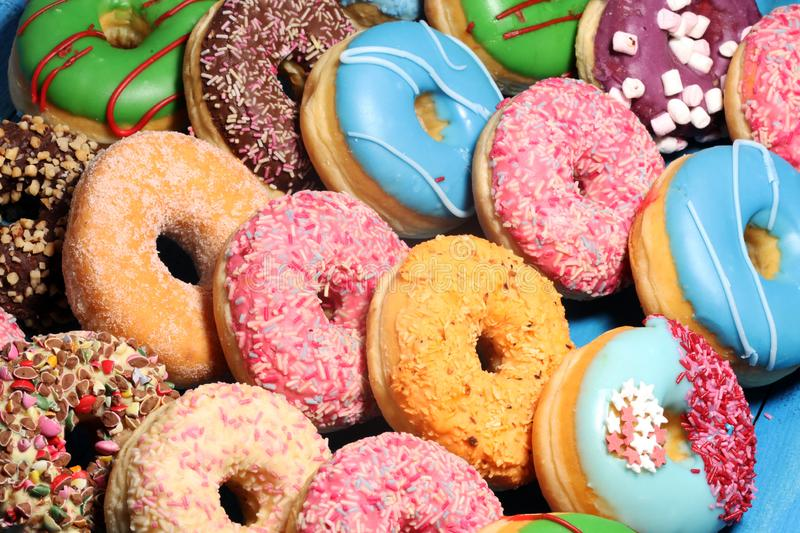 Donuts in different glazes with chocolate. Assorted donuts with chocolate frosted, pink glazed and sprinkles donuts stock images
