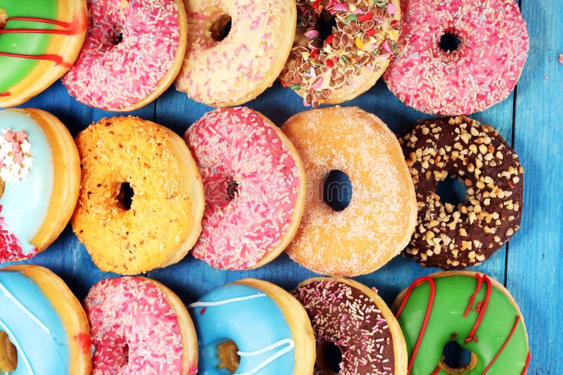 Donuts in different glazes with chocolate. Assorted donuts with chocolate frosted, pink glazed and sprinkles donuts stock photos