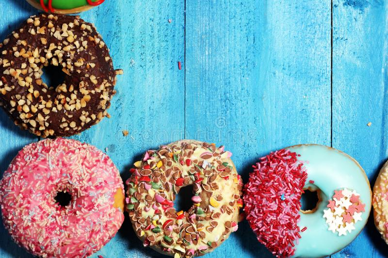 Donuts in different glazes with chocolate. Assorted donuts with chocolate frosted, pink glazed and sprinkles donuts royalty free stock photography