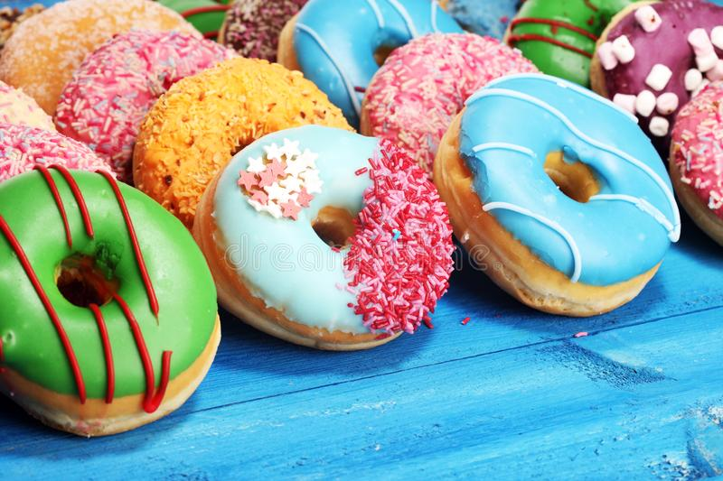 Donuts in different glazes with chocolate. Assorted donuts with chocolate frosted, pink glazed and sprinkles donuts royalty free stock photos