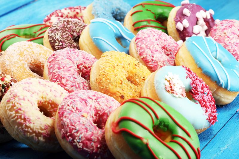 Donuts in different glazes with chocolate. Assorted donuts with chocolate frosted, pink glazed and sprinkles donuts stock photo