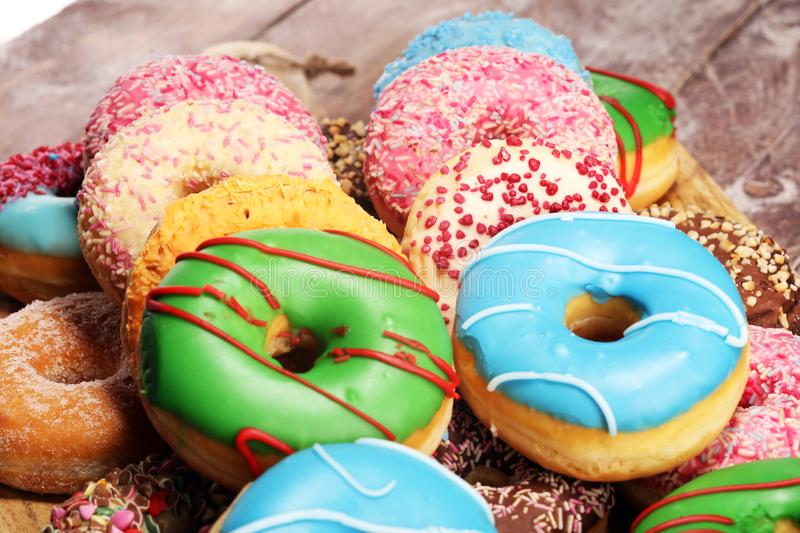 Donuts in different glazes with chocolate. Assorted donuts with chocolate frosted, pink glazed and sprinkles donuts royalty free stock photo