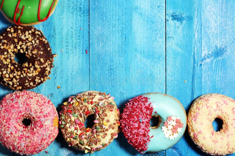 Donuts in different glazes with chocolate. Assorted donuts with chocolate frosted, pink glazed and sprinkles donuts royalty free stock images