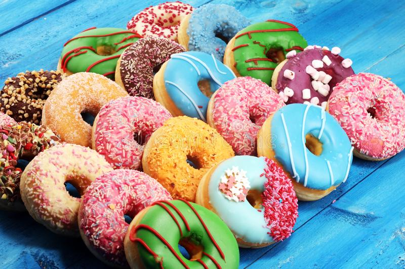 Donuts in different glazes with chocolate. Assorted donuts with chocolate frosted, pink glazed and sprinkles donuts stock photography