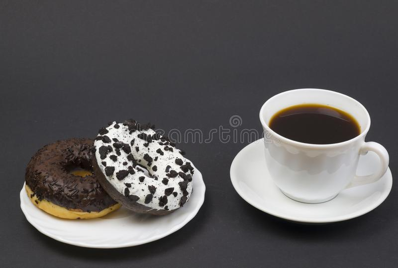 donuts e café de chocolate Two beautiful tasty donuts on a saucer and a cup of aromatic hot coffee fotografia de stock