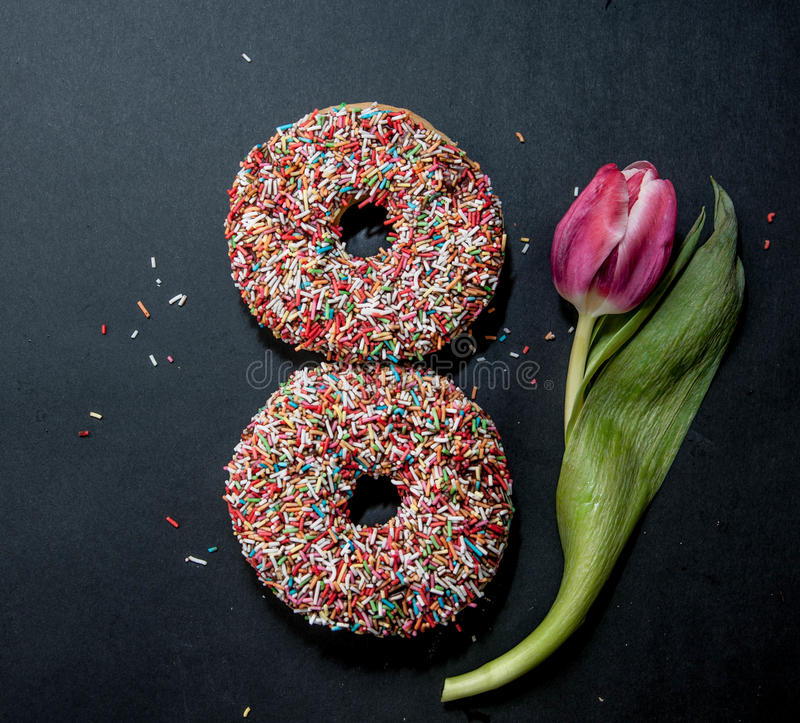 Donuts for eight march and flower on black background royalty free stock photography