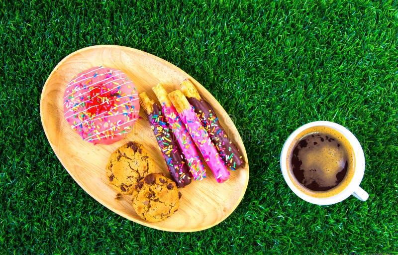 Donuts en zwarte koffie op gras stock afbeelding