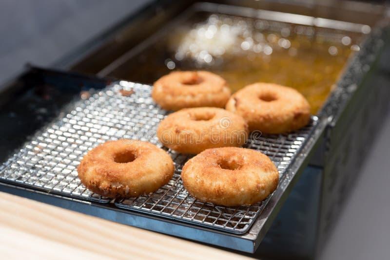 Donuts i selektiv fokus på en kyla kugge med bubblande för varm olja bakom royaltyfri foto