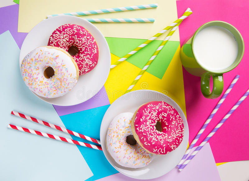 Donuts with icing and milk on pastel colorful background. Sweet royalty free stock photo